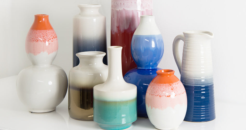 Eight shiny ceramic containers of various shapes, all two-tone white bleeding into a different, vibrant earth-tone color