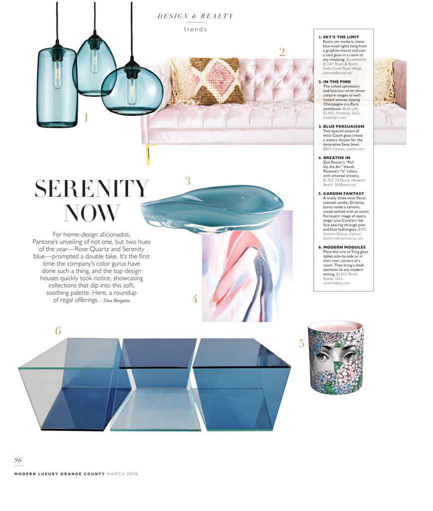 White magazine page, blue-and-pink-colored glass, plastic modules, lighting, and shiny, pink, tufted sofa with throw pillows