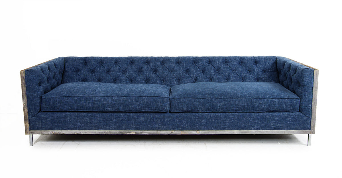 Modern blue denim colored sofa with straight arms, two cushions, an aged wood frame and tufting on the back and arms.