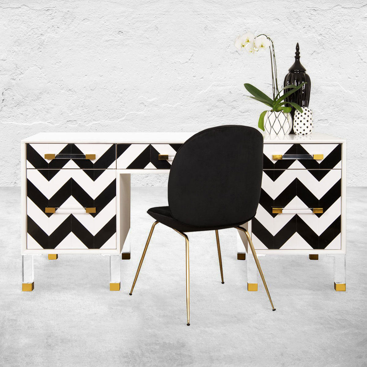 Simple black chair with metal legs in front of a six-drawer desk with a white frame, black-and-white chevron front and combination Lucite and brass legs.