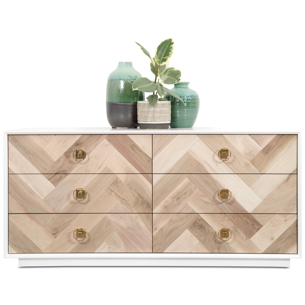 Six-drawer dresser with a white pedestal base, a wood plank chevron facade, brass and acrylic drawer pulls and an arrangement of two green vases and a plant centered on the top.