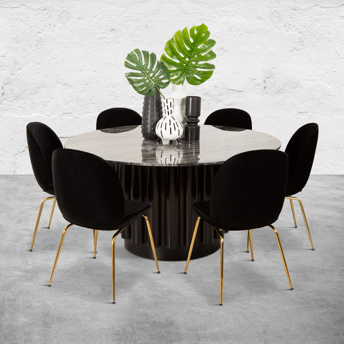 Round dining table with a black columnar base, a black marble top and six black upholstered chairs with brass legs.