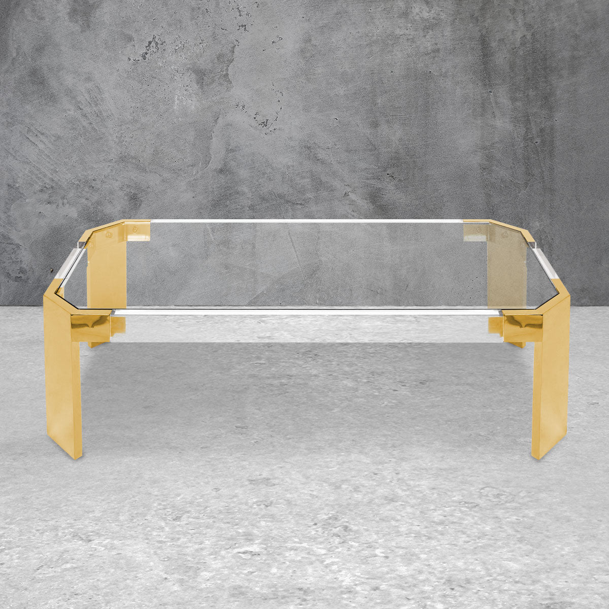 Rectangular coffee table with a clear Lucite top and brushed brass legs.