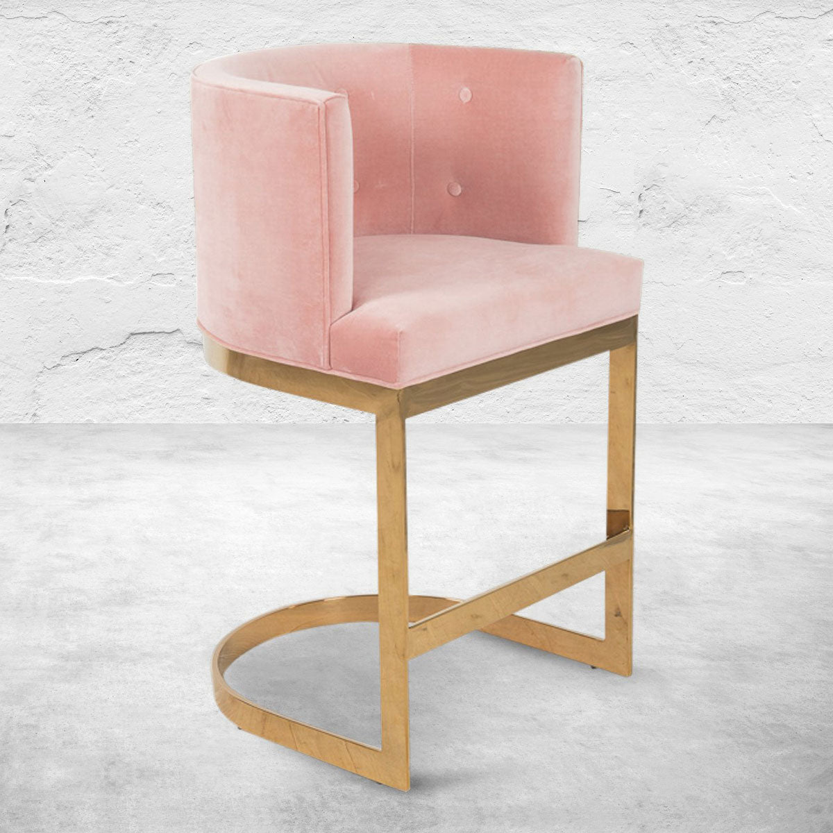 Art Deco style bar or counter stool with velvet blush upholstery, mid-rise back, button tufting and polished brass base.