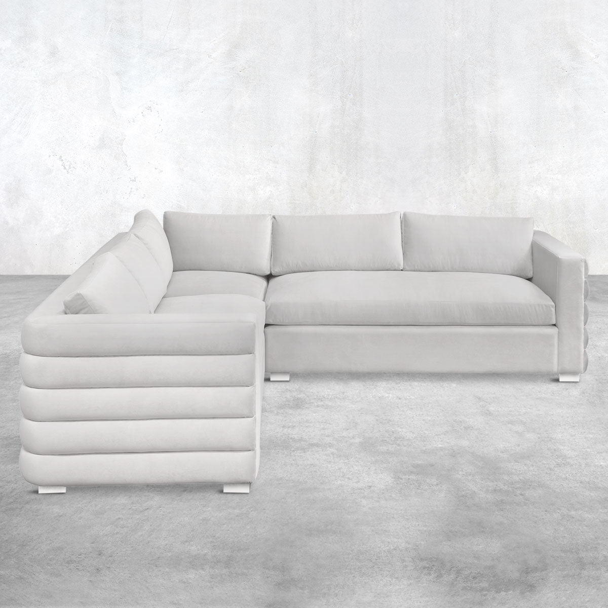 Light gray L-shaped three-piece sectional with pin feet, a pillow back, straight arms and horizontal channel-tufted upholstery on the outside.