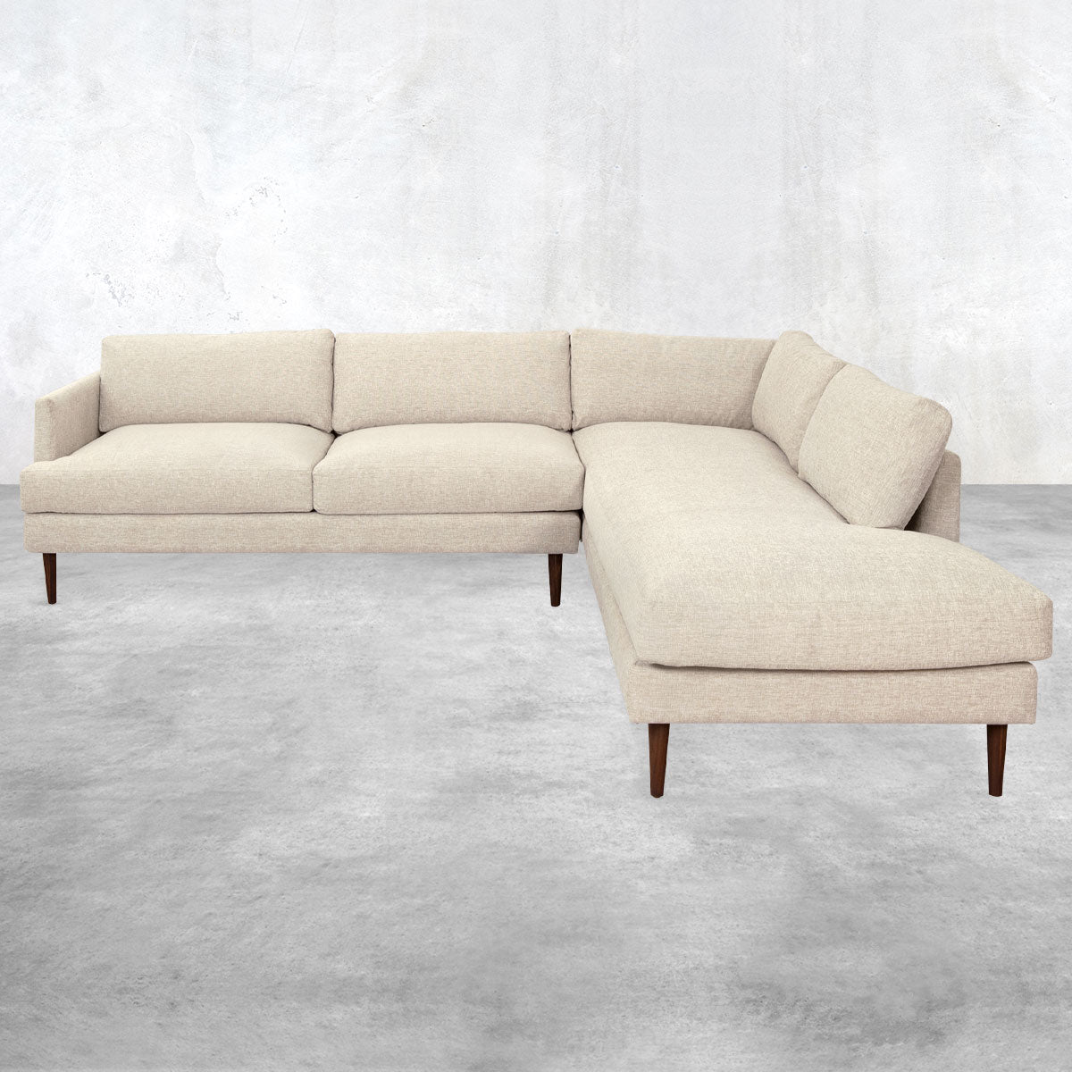 Two-piece sectional sofa with a chaise end, overstuffed pillow back, brown cone legs and light beige upholstery.