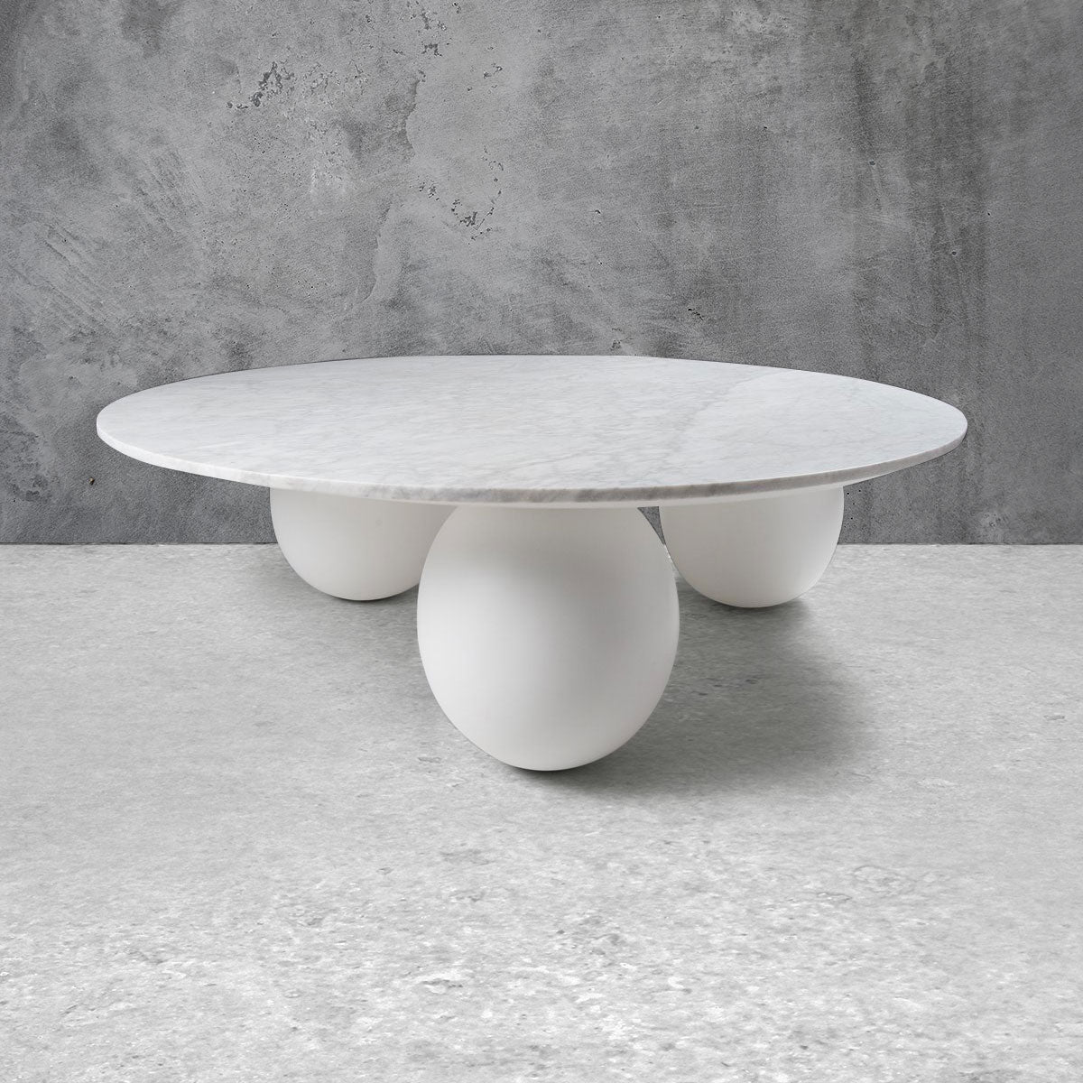 Modern round coffee table with three spherical legs in white and a light marble top.