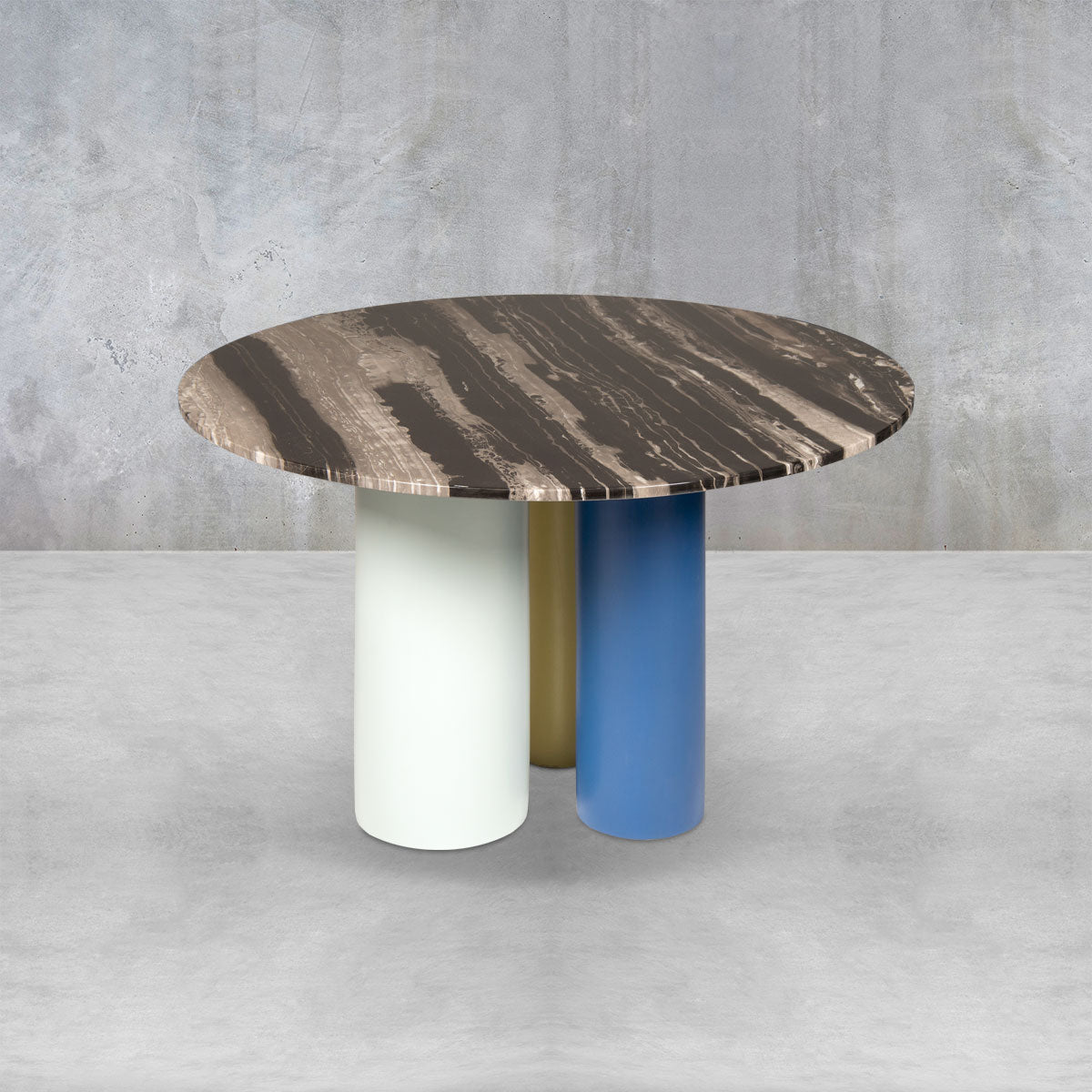 Round dining table with a dark distressed wood top and three large support columns in white, blue and yellow.
