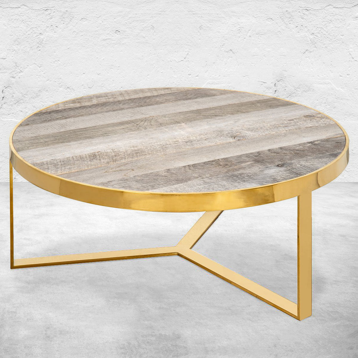Circular coffee table with three legs, brass frame and weathered wood plank top.