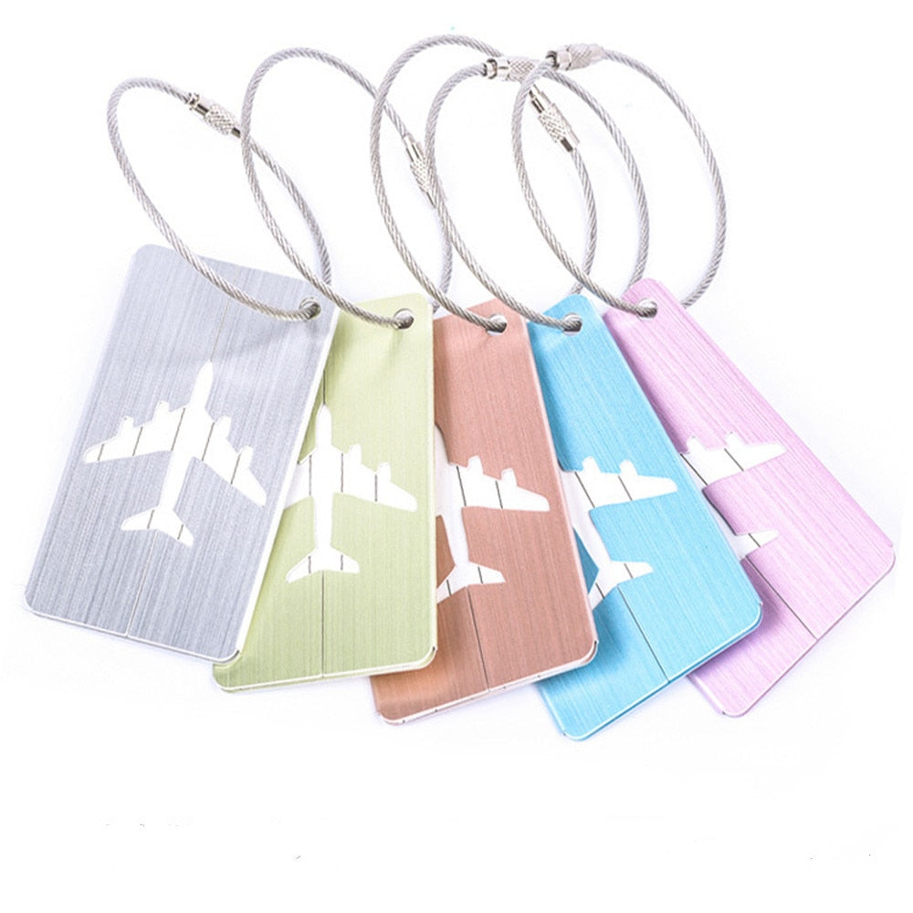 different colour aluminium luggage tags on white background