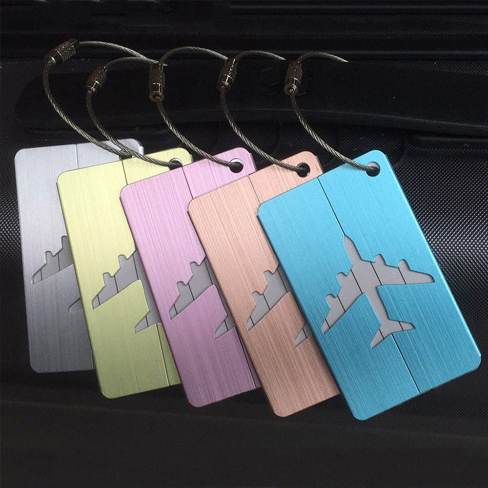 five different colour aluminium luggage tags