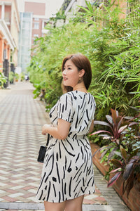 back view of plus size white and black graphic print zip front dress