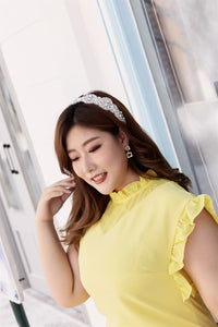 Close up of plus size yellow ruffle neck and sleeve shift dress