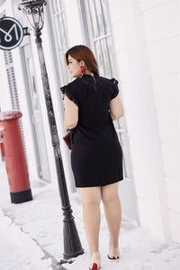 Back view of plus size black ruffle neck and sleeve shift dress