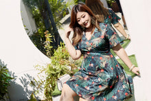 Load image into Gallery viewer, plus size black and green tropical print faux wrap fit and flare dress