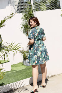 back view of plus size blue and green tropical print faux wrap fit and flare dress