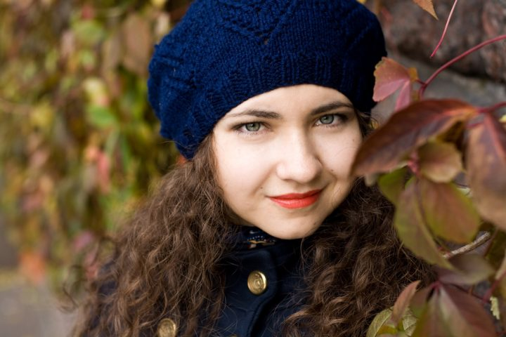 Women wearing beret with long curly hair.