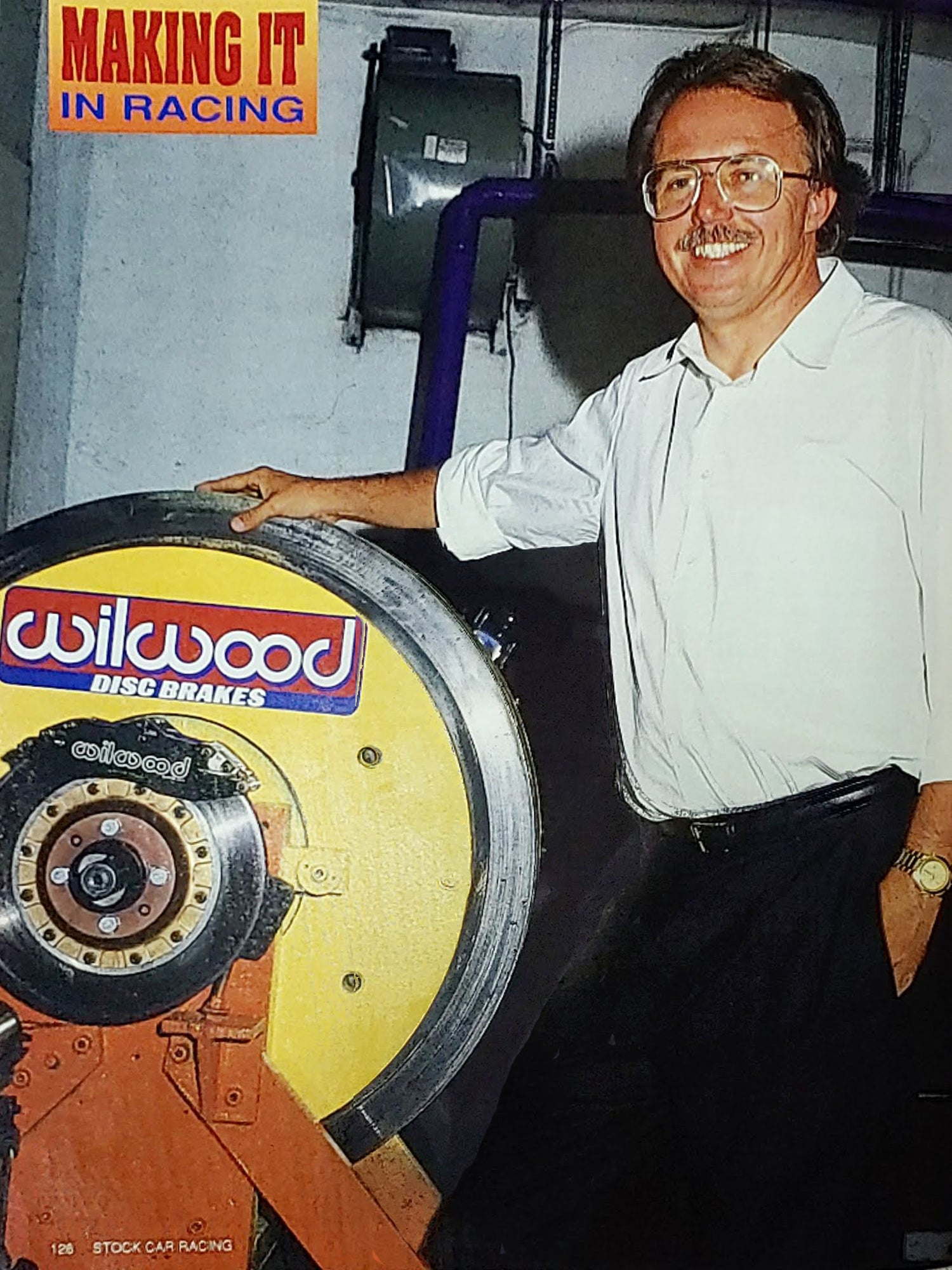 Bill Wood stands next to the Wilwood brake dynamometer he developed