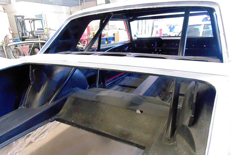 Roll cage and mini tubs in rear of Mustang