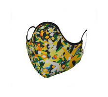 Load image into Gallery viewer, This 100% cotton face mask is yellow, green, white and blue with black edging and black cloth ear ties. The bright and floral pattern is semi abstract and based on Annika Connor's Avalon oil painting. The mask has ties which first you knot to adjust to best fit your face, then you loop around your ears. The face mask itself covers your nose, mouth, and goes under your chin. The inside of the mask has matching 100% cotton fabric which creates a pocket for you to be able to insert a filter of your choice.
