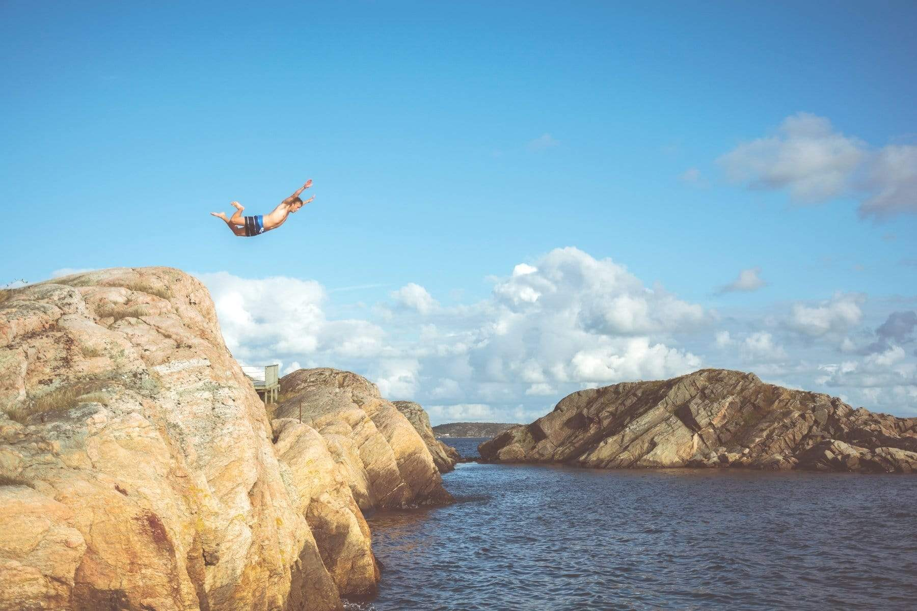 Man leaps off cliff into water