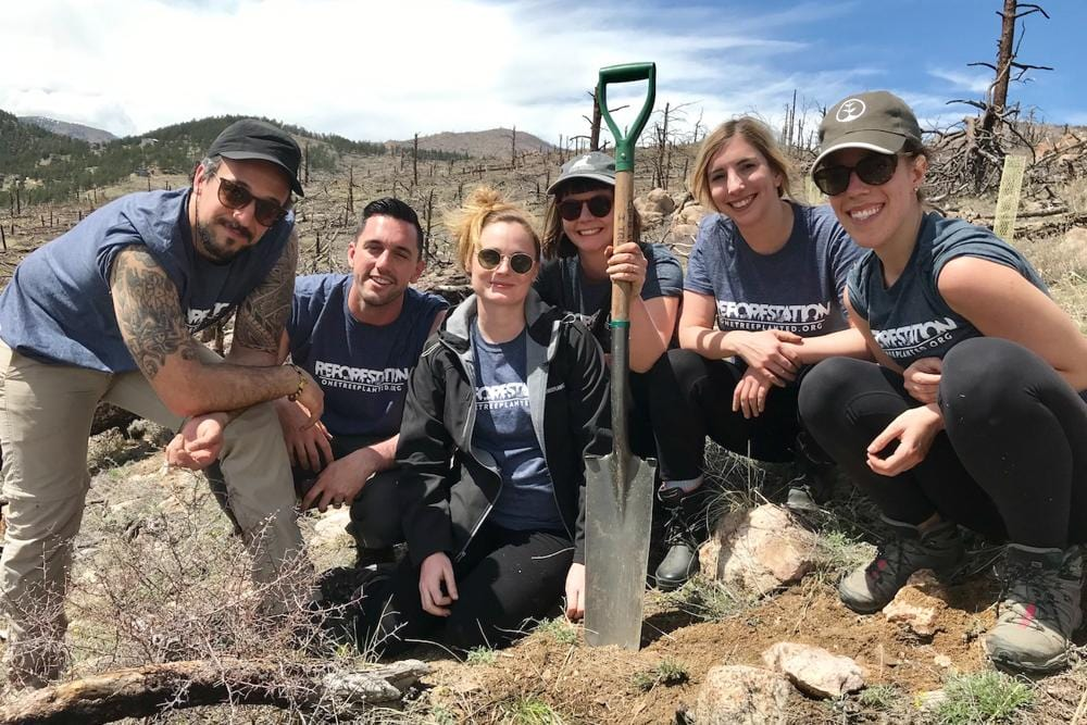 Group of One Tree Planted staff with a shovel outdoors on a mountain