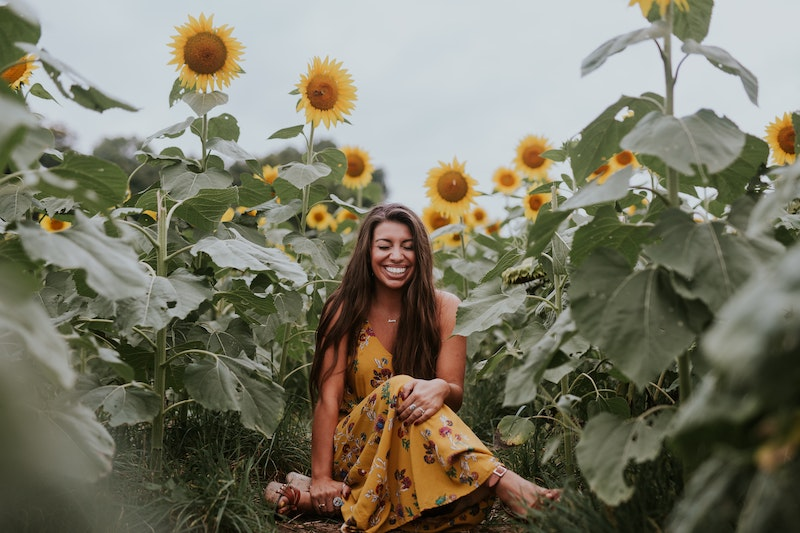 woman wearing yellow dress sitting in a sunflower field with many big green leaves and yellow sunflowers