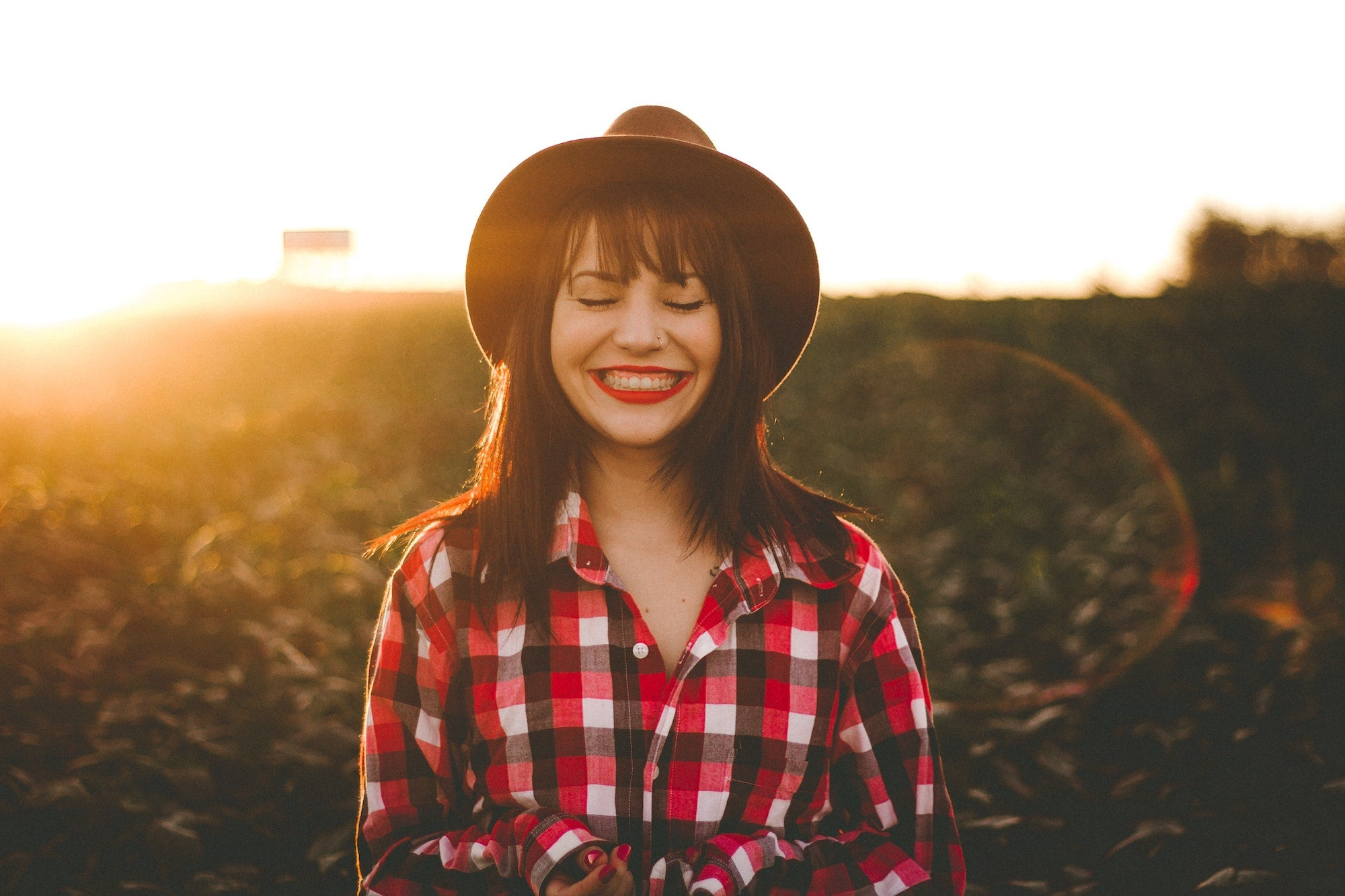 Woman in plaid shirt and hat, smiling with her eyes closed during golden hour