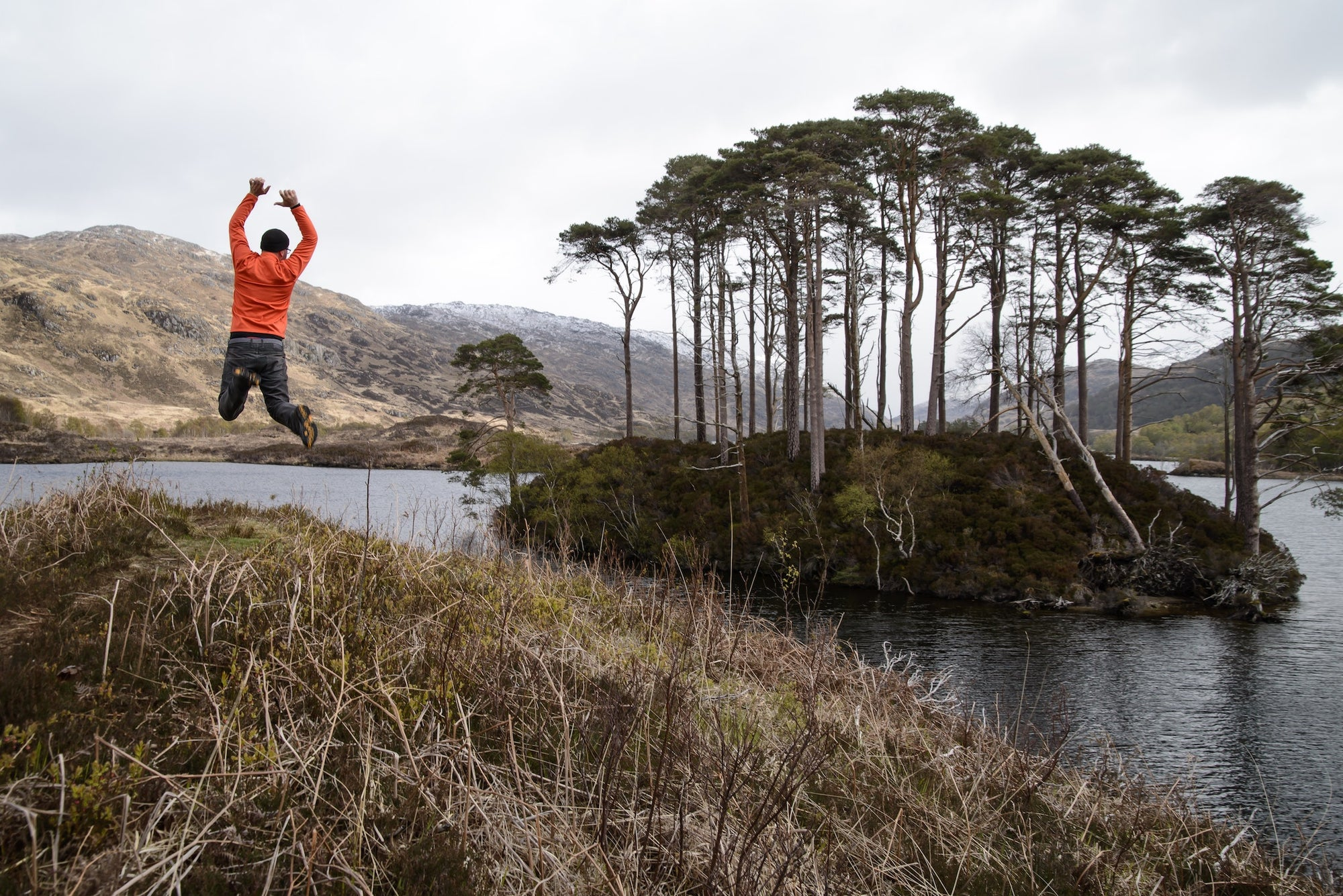 man jumping in the outdoors with trees and lake in background