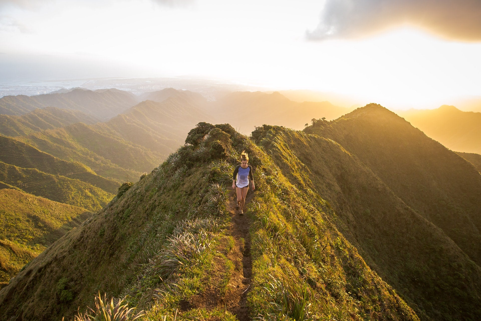 young woman hiking on lush green mountaintop with sunrise and distant mountain ranges in background