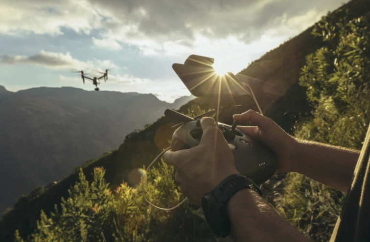 person flying a drone in the forest
