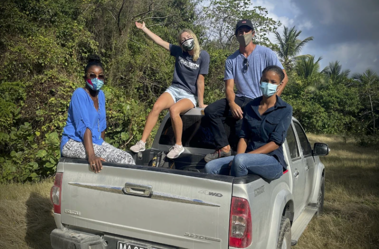 People sitting in truck bed in forest