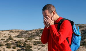 man hiking with his ears clogged