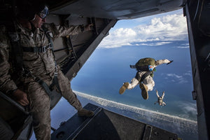 military man jumping out of plane