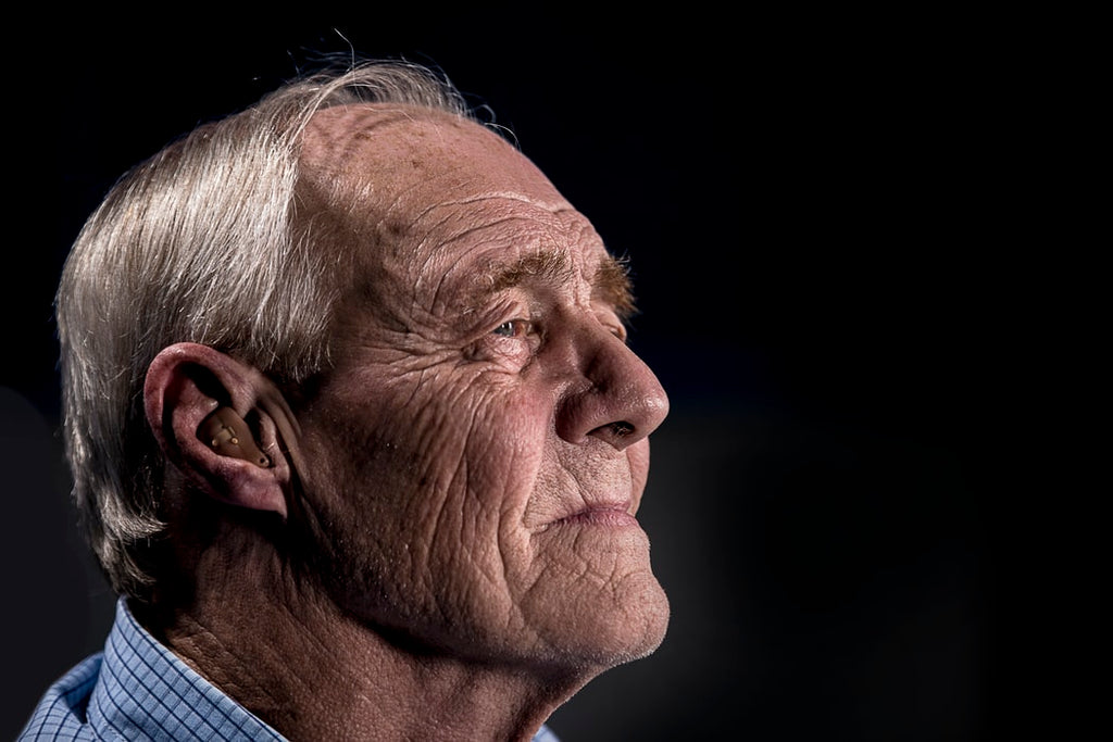 older man with hearing aid that isn't included in Medicare coverage