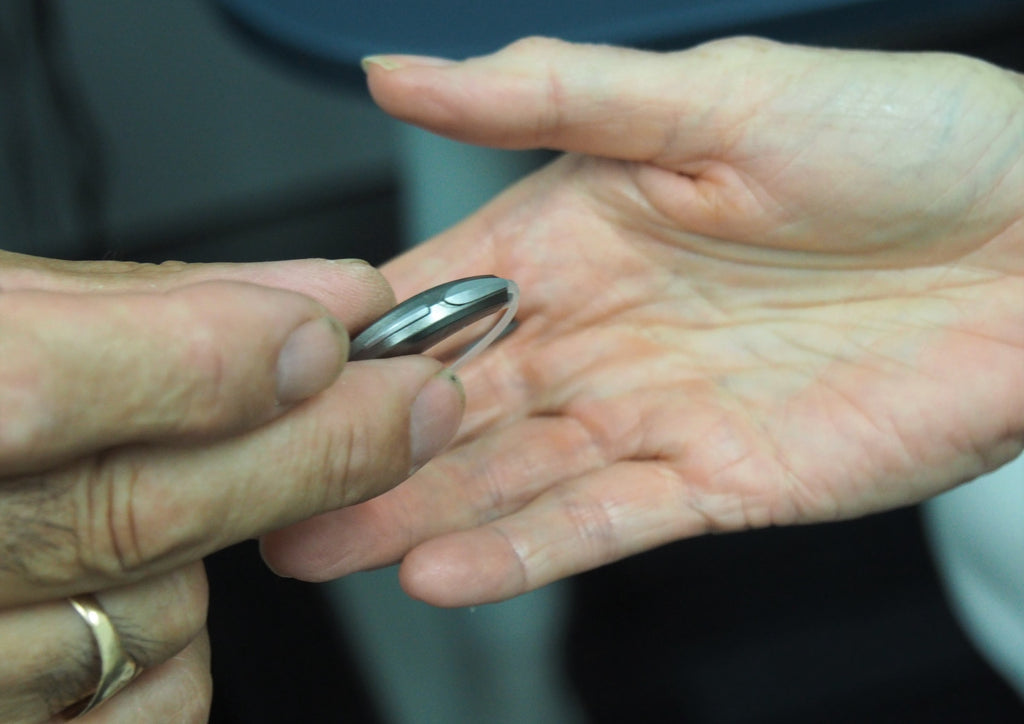 person holding a BTE hearing aid