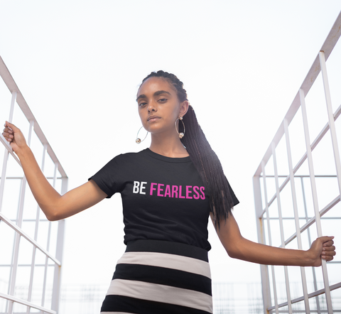 black woman with natural hair braids in black t-shirt with white and pink be fearless logo
