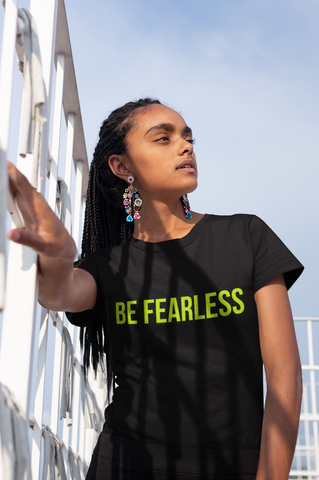 black woman with natural hair braids in black t-shirt with fluorescent green be fearless logo