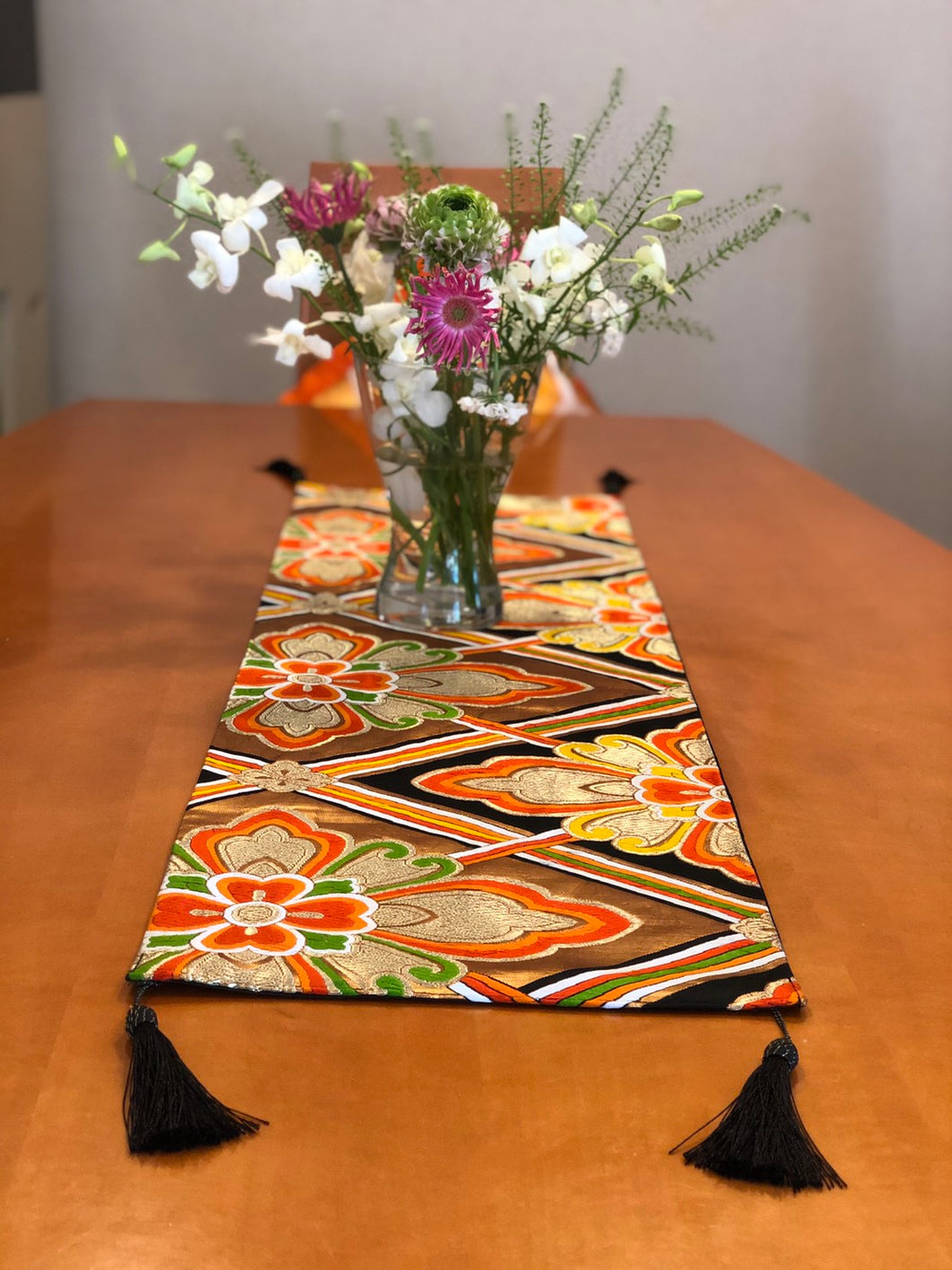 Table Runner in gold on black Hanabishi motif with black tassels.