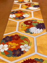 Load image into Gallery viewer, Table Runner in gold with a Hanamaru (flower circles) pattern on a turtle shell motif.