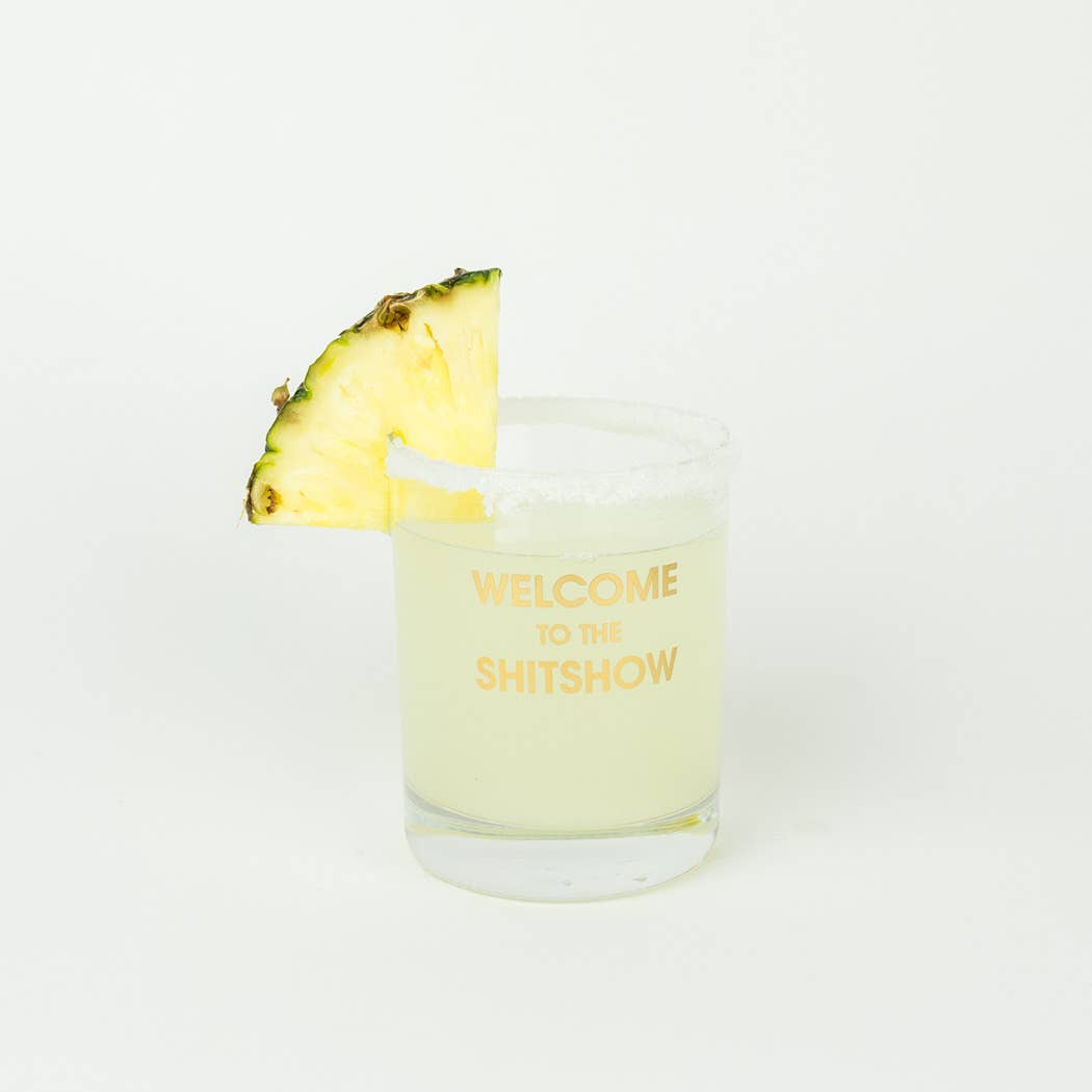 "Crush your cocktail in style with this ""Welcome to the Shitshow"" gold foil rocks glass.  Rocks glasses are printed in Los Angeles. 13.25 oz. American made rocks glass gold foil imprint hand wash only"