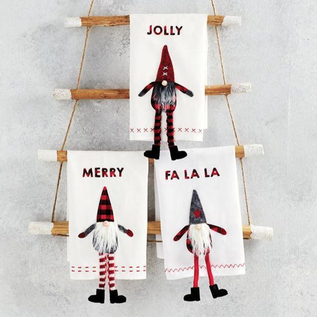 "A holiday folklore favorite, these decorative gnomes will add a whimsical touch to your holiday decor.  These linen hand towels feature buffalo check flannel sentiment applique, hemstitching and felt and buffalo check dangle leg gnome applique with knit, faux fur beard and wooden nose details.  Sold indivdually - choose from Jolly, Merry or Fa La La. Size: 21"" x 14"""