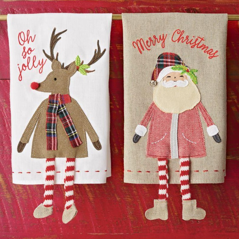 "Holidays and plaid always go hand in hand. Add this whimsical take on a classic holiday design to any sink side. The linen hand towel features embroidered sentiment and felted wool, canvas and cotton character applique with knit dangle legs and pom-pom and jingle bell details.  Size: 14"" x 21"" Each sold separately."