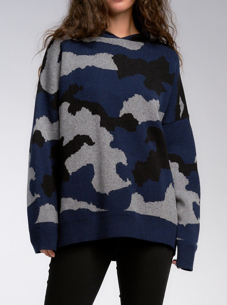 This edgy camo print hooded sweater is perfect for those cooler temps. We love the stunning camo print in shades of deep blue, grey, and black - with its hooded look it's the look of the season! Pair it with your favorite blacks, denims, whites or leggings. It will go with almost anything, the possibilities are endless!   Generous fit, if between sizes size up. 47% VISCOSE, 28% POLYESTER, 25% NYLON