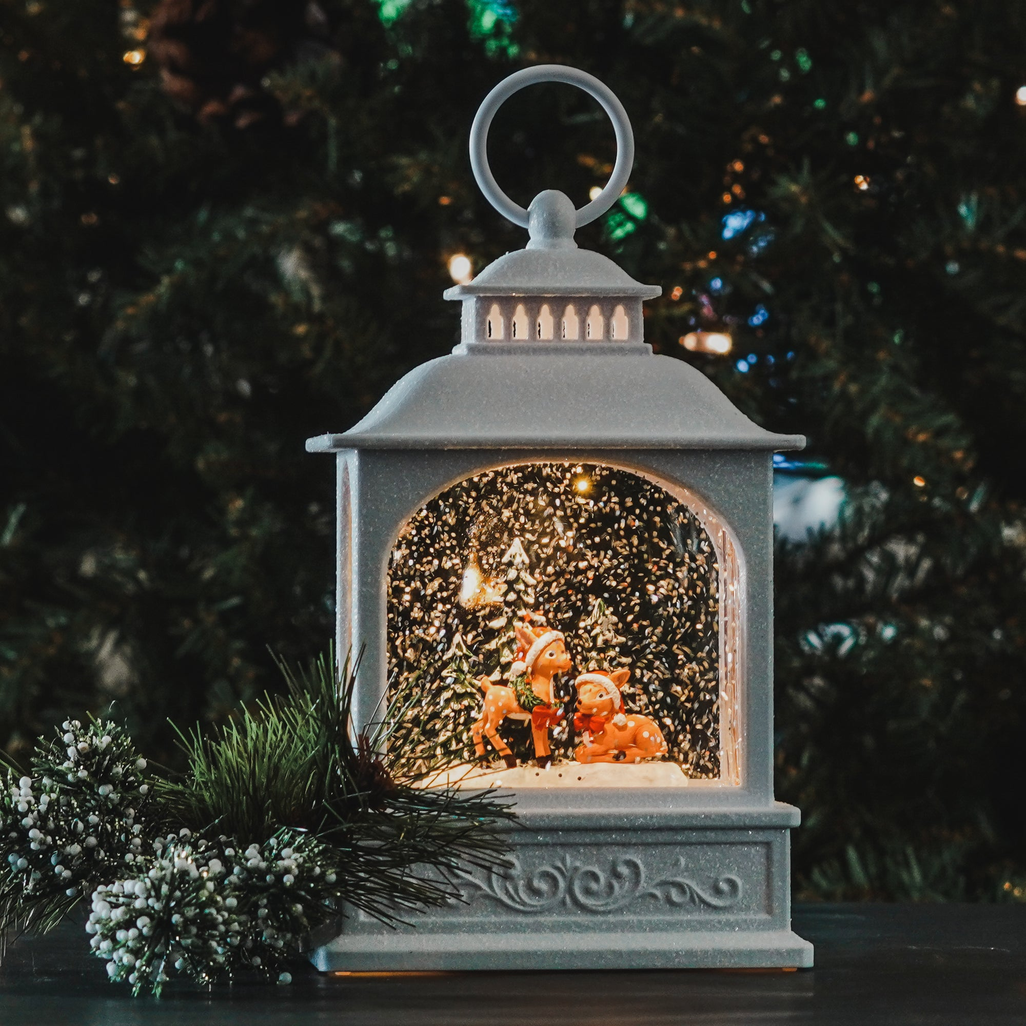 Darling white glitter lantern with 2 Deer inside surrounded by evergreen trees. 8.25 Inch White Glitter picture window water lantern featuring a Christmas Scene, with swirling glitter. A must have addition to your Holiday traditions.