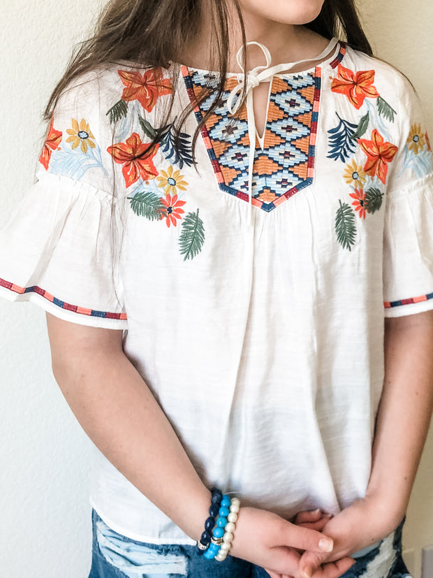 Looking for paradise? Grab this embroidered print, peasant tie neckline and sleeve ruffles and head off to paradise! Pair with your favorite denim or shorts add some tan sandals and away you go!