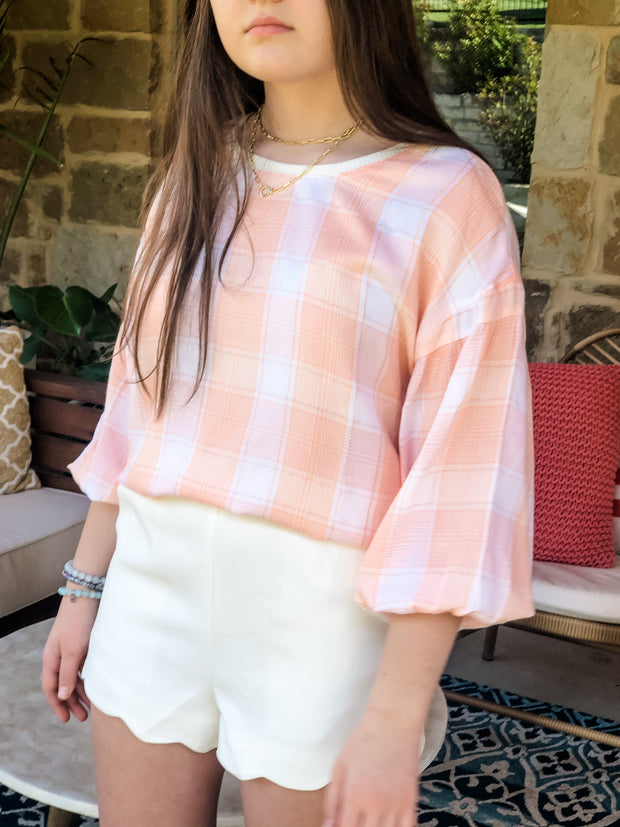 Embrace the love in this on trend peach lightweight plaid top. Perfect for work or play it can be dressed up and down with ease. We love the balloon sleeves and jersey kint detail around the crew neckline. Paired with our Sweet on Me Summer Shorts.
