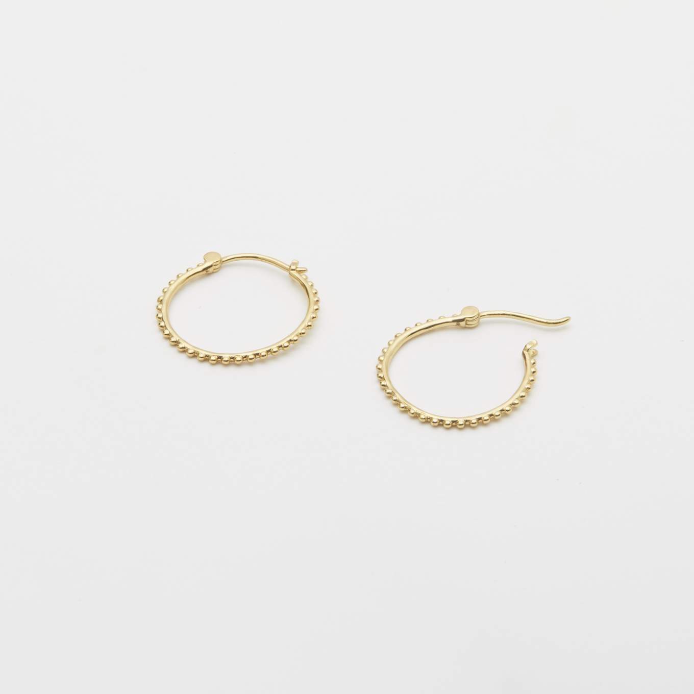 "The Gorjana Bali Small Hoops are the perfect size earring with a classic Bali beaded design, these huggie hoops are effortlessly chic and easily pairs with any outfit. 3/4"" in diameter. Hinge closure. Available in 18k gold plated brass."