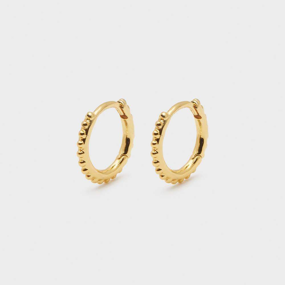 "The Gorjana Bali Huggies are the perfect gold earrings in our classic Bali beaded design are meant to be worn every day and never take off. 9/16"" in diameter Hinge closure Available in 18k gold plated brass."
