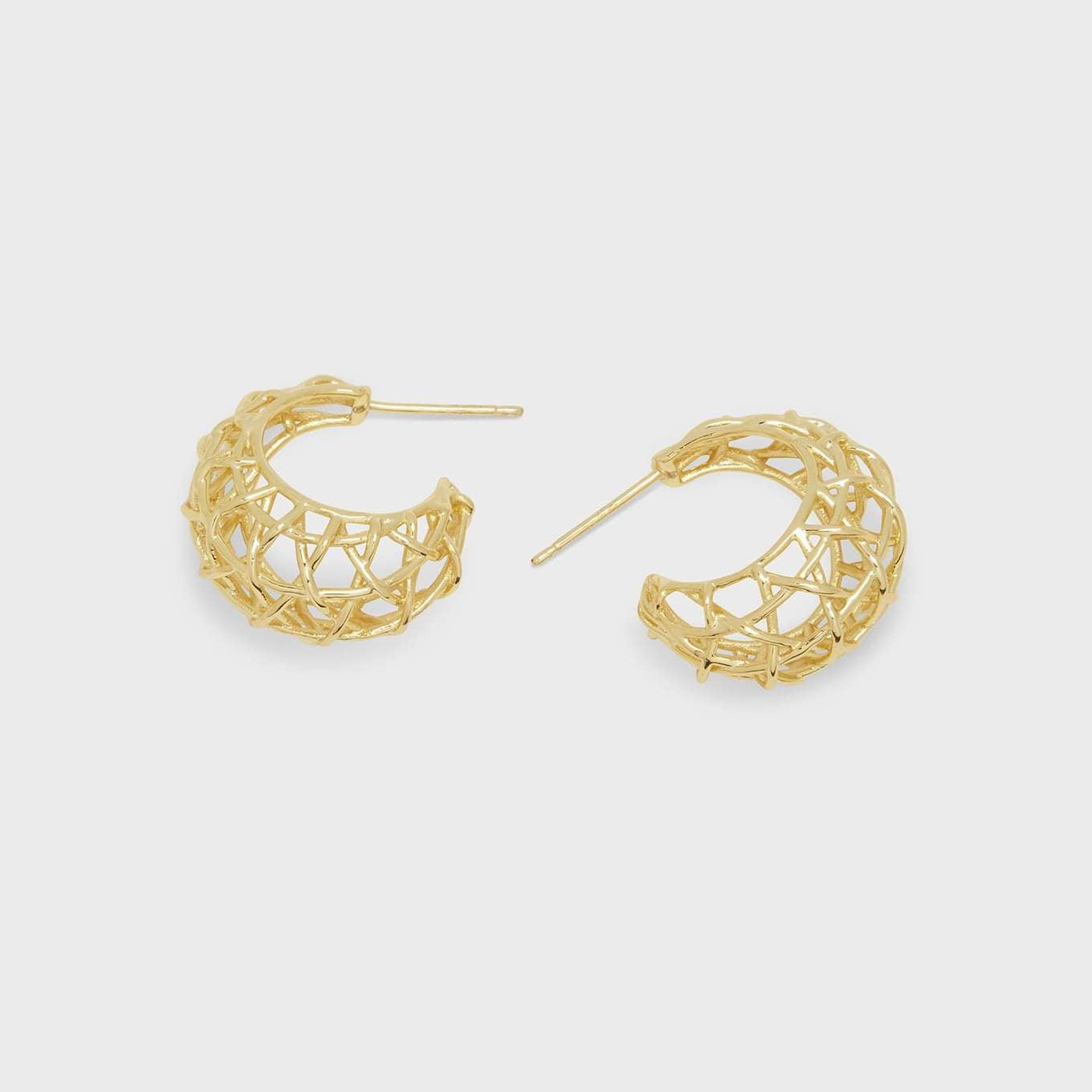 "We refreshed the classic gold hoop earring with a much needed dose of texture inspired by the beautiful artisan textiles of Mexico. A lightweight hoop with major style impact.  7/8"" profile diameter 1/2"" wide Post back 18k gold plated brass Avoid contact with anything containing derivatives of alcohol"